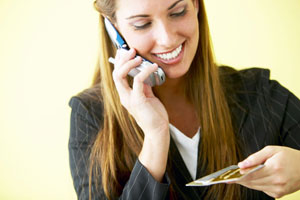 Picture of a woman smiling on phone with a credit card in hand